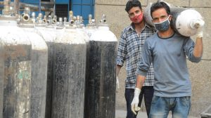 Workers carry medical oxygen cylinders-The Dispatch